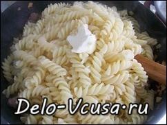 Высыпаем макароны к обжаренным сальсичи и добавляем при желании немного сливочного масла