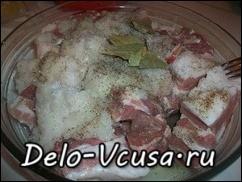 Кладем ребрышки в форму для запекания и добавляем туда перемолотый лук и чеснок, добавляем соль, перец, лавровый лист, и другие специи на Ваш вкус
