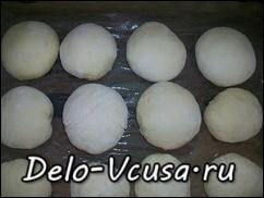 Кладем пирожки швом вниз на смазанную маслом форму