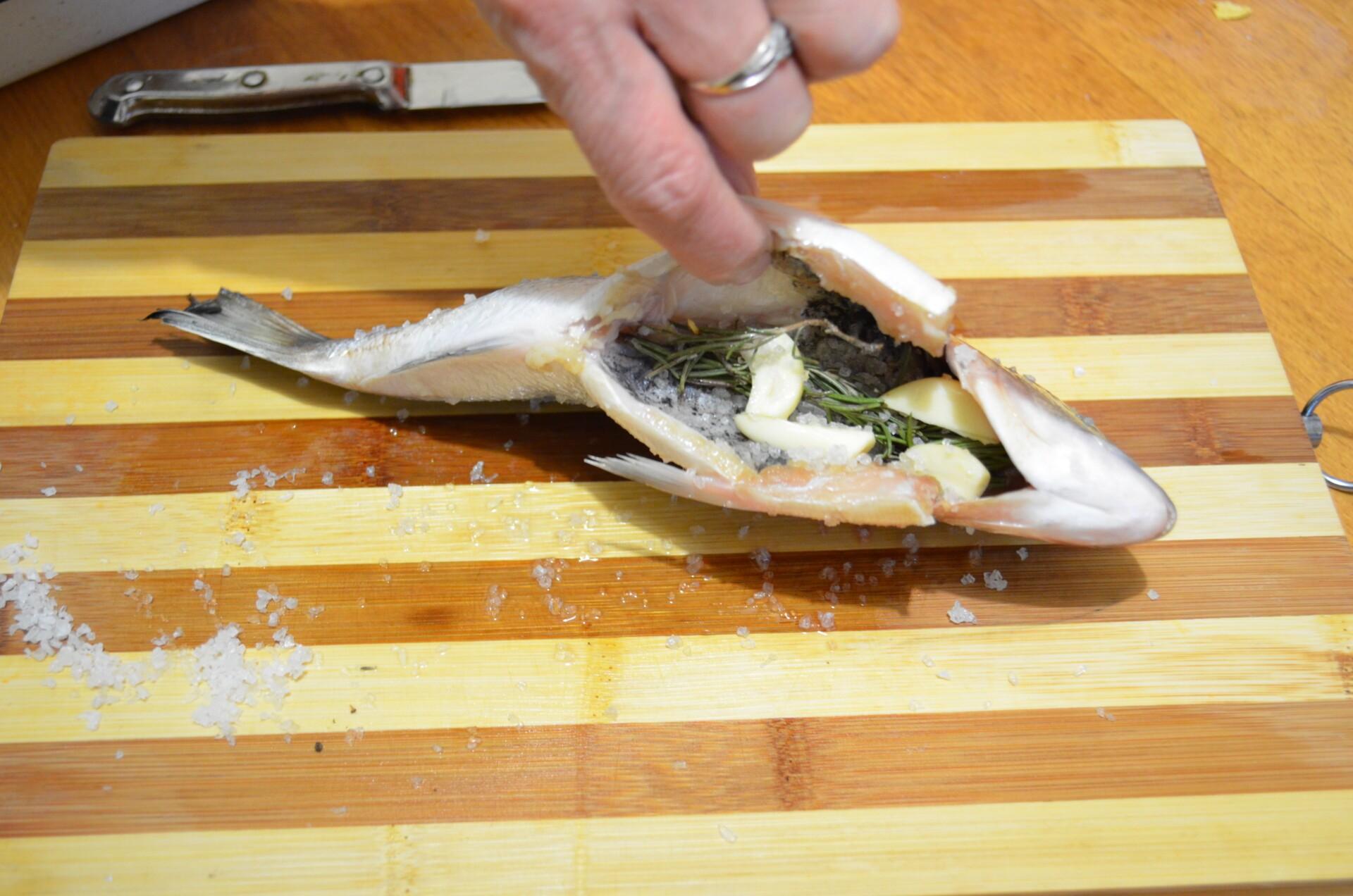 Дорада жареная с розмарином и чесноком: Кладем в брюшко рыбы чеснок и розмарин