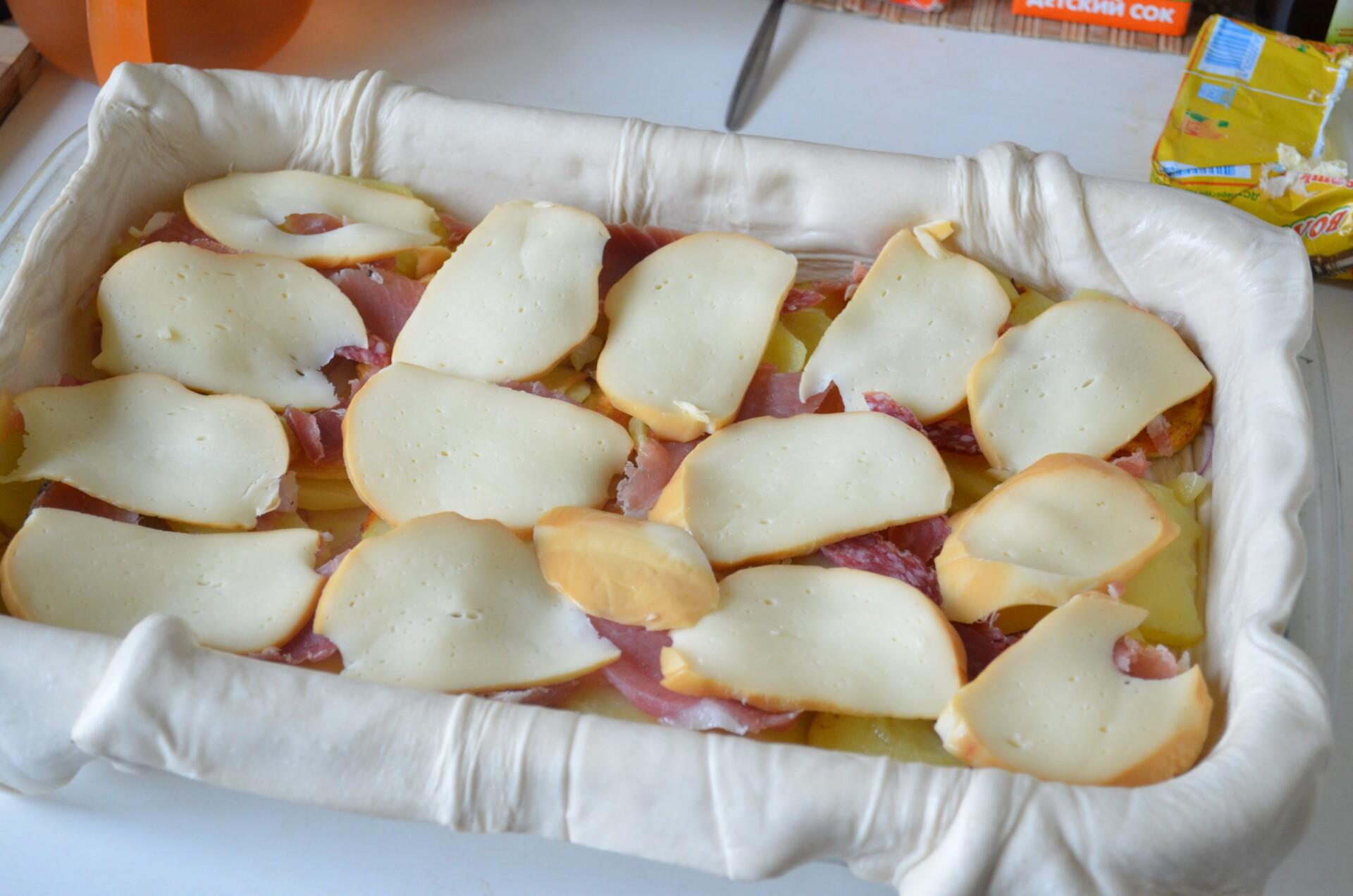 Сверху кладем слой сыра, слегка солим и перчим пирог