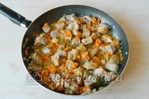 Плов со свининой на сковороде: Добавляем к мясу нарезанный лук и тертую морковь