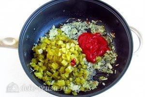 Салат с кальмарами и солеными огурцами: Добавляем к луку огурцы и томатную пасту