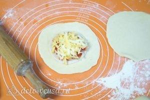 Булочки с колбасой и сыром: Раскатать тонко один кусочек теста и выложить начинку