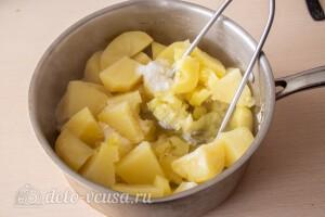 С картошки сливаем жидкость, добавляем соли и мнем в пюре
