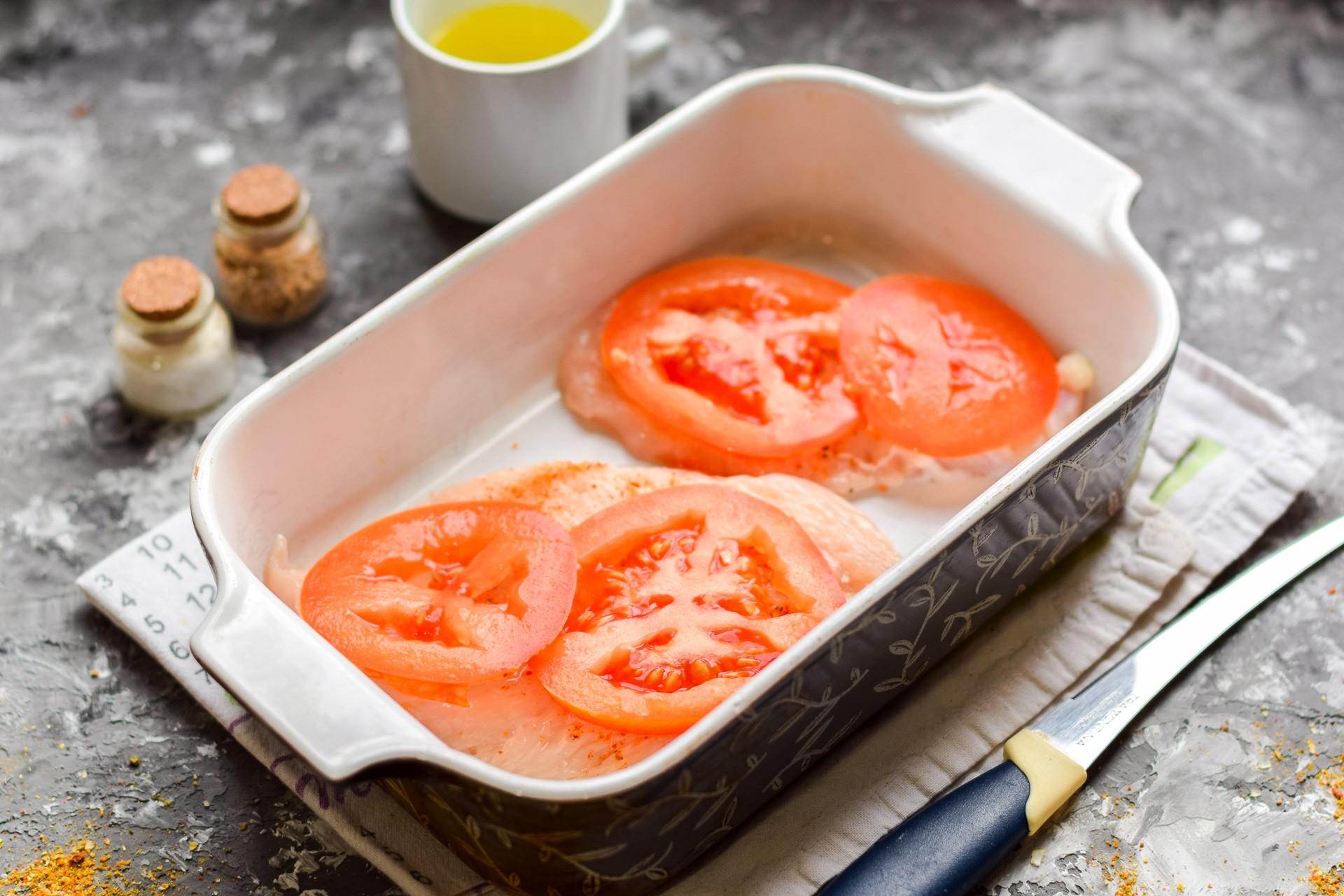 Кладем филе в форму, а сверху кладем ломтик помидора