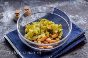 Соленые огурцы режем кубиками и добавляем в салатник