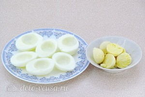 Вареные яйца разрезаем пополам и разделяем на белки и желтки
