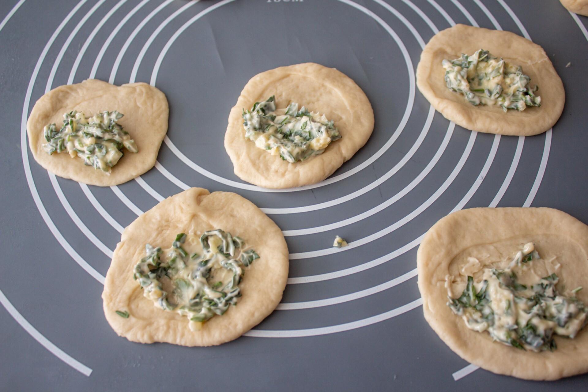 Раскатываем тесто в лепешки и смазываем начинкой