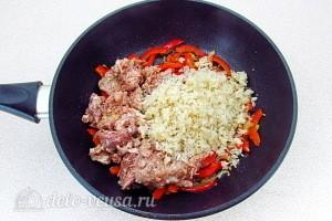 Добавляем в сковороду тушенку и рис