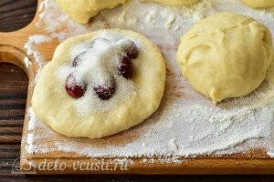 Раскатываем тесто в лепешку и кладем сверху вишни и сахар