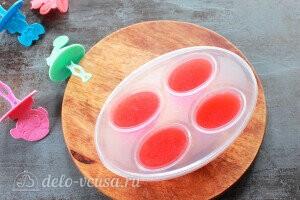 Наливаем клубничный сок в формочки для мороженого