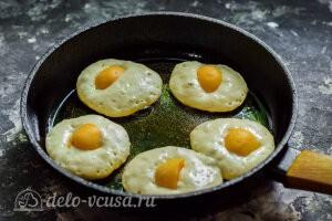 Ложкой выкладываем тесто на сковороду и клаедм в центр половинку абрикоса