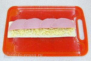 На полоску теста кладем полукольца колбасы и тертый сыр
