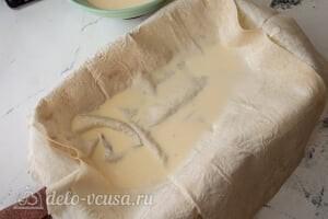 Пирог из лаваша с тушеной капустой: Кладем на дно формы два листа лаваша и добавляем немного заливки
