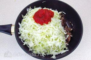 Тушеная капуста с куриными сердечками: Добавляем капусту, томатную пасту и воду в сковороду